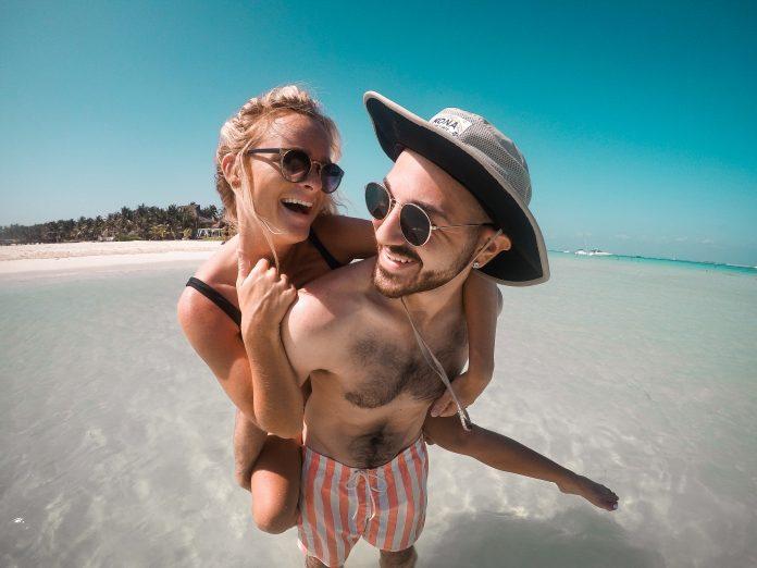 Happy couple on beach. Photo by Joey Nicotra on Unsplash