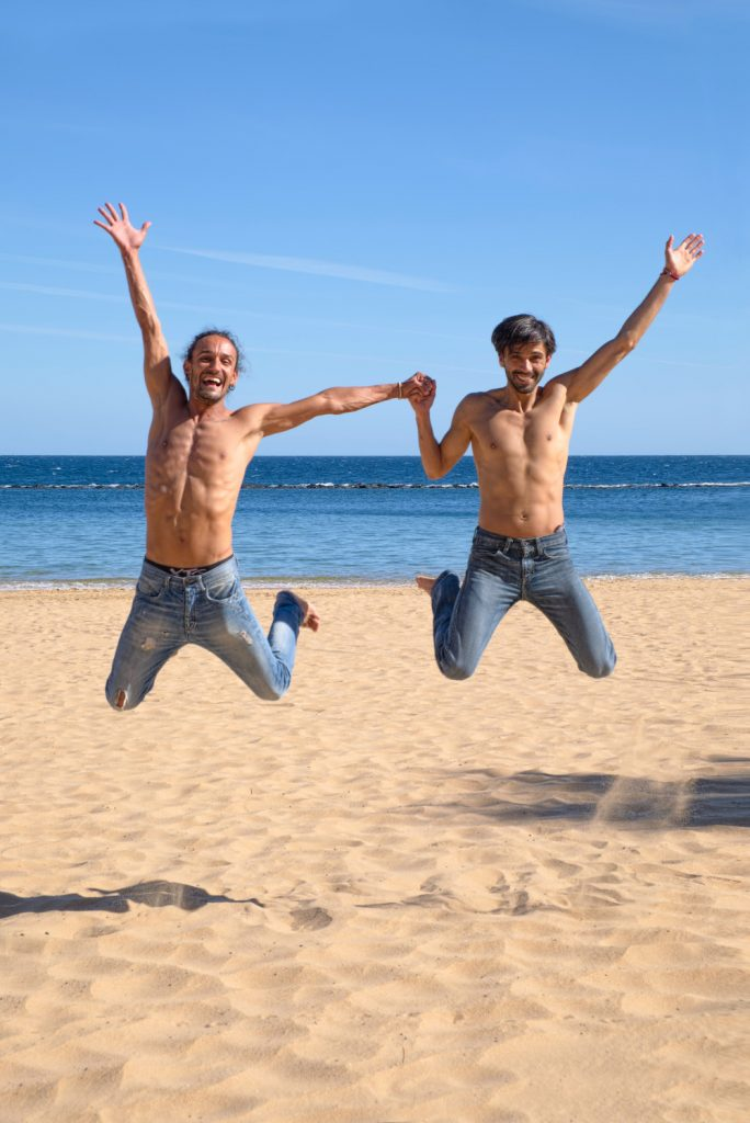 Two shirtless LGBT men at a beach jumping in the air while holding hands