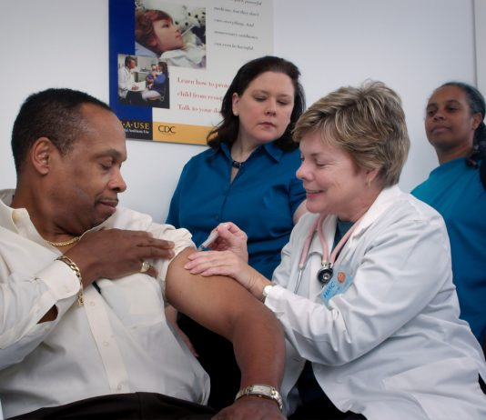 Nurse giving a man a vaccination - photo courtesy of Centres for Disease Control and Prevention (CDC) - via Unsplash